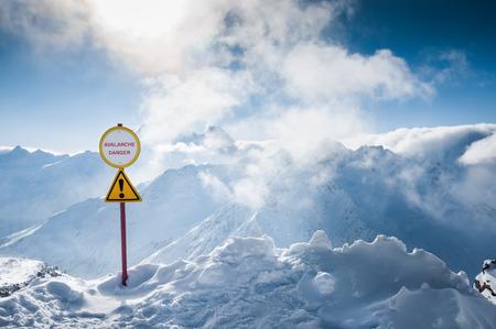advertencia: Estaci�n de esqu� de Elbrus. C�ucaso, Rusia. Se�al de advertencia de peligro de aludes. Hermoso paisaje de invierno con las monta�as cubiertas de nieve y el cielo azul Foto de archivo