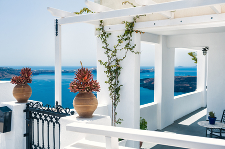 Greek house with terrace and sea view. White architecture on Santorini island, Greece. Beautiful summer landscape