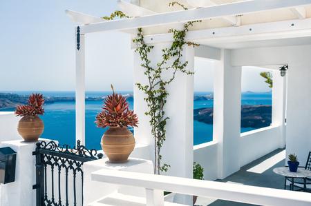 Grecki dom z tarasem i widokiem na morze. Biały architektura na wyspie Santorini, Grecja. Piękny krajobraz lato