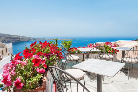 Terrace with flowers. Oia, Santorini island, Greece. Beautiful summer landscape with sea view. Selective focus