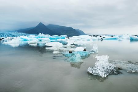 fjallsarlon: Icebergs in the glacial lake with mountain views. Vatnajokull glacier, Fjallsarlon lagoon, the South coast of Iceland Stock Photo