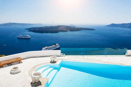 summer house: Swimming pool with sea view. White architecture on Santorini island, Greece. Beautiful landscape with sea view Stock Photo
