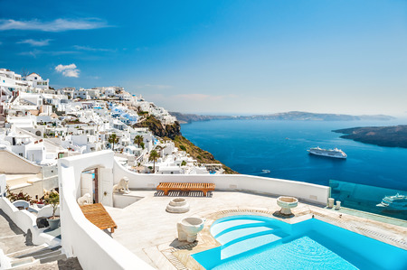 mediterranean houses: White architecture on Santorini island, Greece. Swimming pool in luxury hotel. Beautiful view on the sea