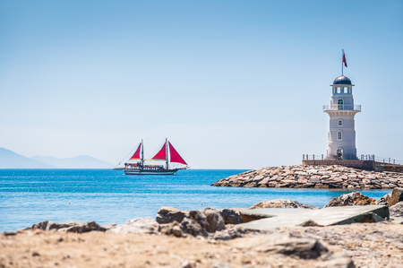 Lighthouse and tourist yacht by the sea. Sea beach in Alanya, Turkey. Beautiful summer landscape