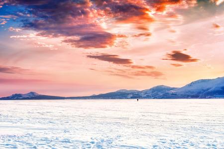 frozen lake: Fantastic winter landscape with frozen lake. Dramatic sky. Beautiful sunset