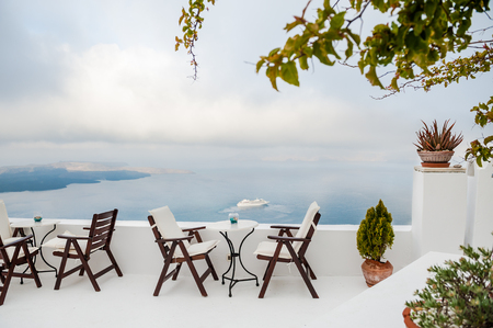 Cafe on the terrace with a beautiful sea view. Foggy morning. White architecture on Santorini island, Greece