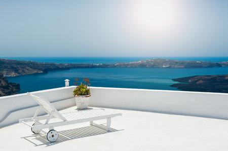 Sunbed on the terrace. White architecture on Santorini island, Greece. Beautiful view on the sea Standard-Bild