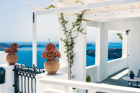 mediterranean houses: Greek house with terrace and sea view. White architecture on Santorini island, Greece.  Beautiful summer landscape