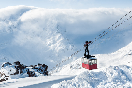 Old red cable car at Elbrus mountain. Ski resort Elbrus. Caucasus, Russian Federation. Beautiful winter landscape with snow covered mountains. Stock Photo
