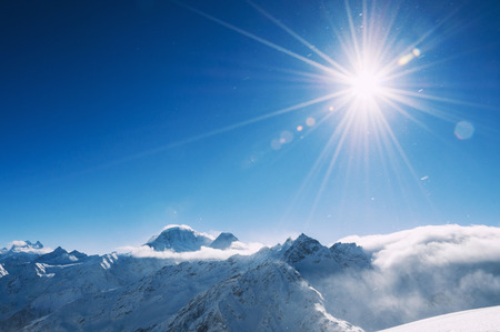 snow covered mountains: Winter snow covered mountains at sunny day. Ski resort Elbrus. Caucasus, Russian Federation. Beautiful winter landscape Stock Photo