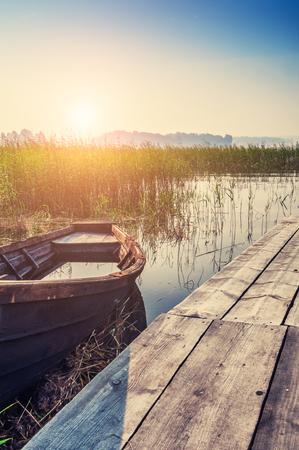 lake sunset: Old boat on the coast of lake at sunset. Beautiful summer landscape. Creative vintage filter, retro effect