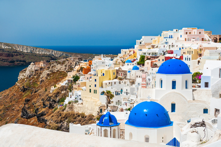 Church with blue domes in Oia town. White architecture on Santorini island, Greece.