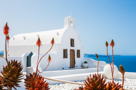 Church in Oia town, white architecture on Santorini island, Greece. Beautiful landscape with sea view. Selective focus