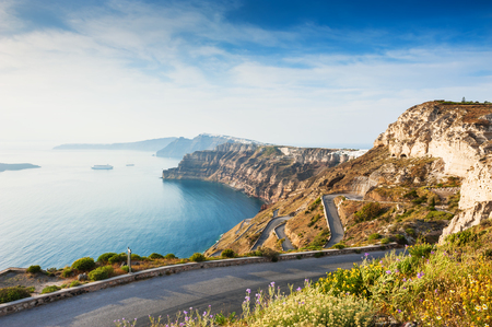 Mountain road to the port on Santorini island, Greece. Beautiful summer landscape with sea view at sunset