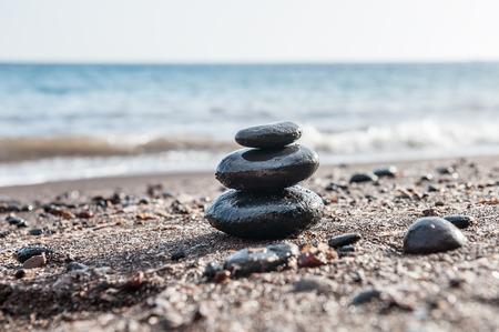 Kamienie piramida na plaży, morza w tle. Zen i harmonia. Mała głębia ostrości