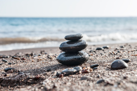 Stones pyramid on the beach, sea in the background. Zen and harmony. Small depth of field