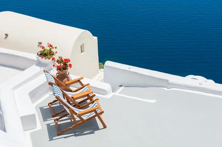 greece: Sunbeds on the terrace of a hotel. Santorini island, Greece. Beautiful summer landscape with sea view