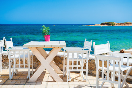 greece shoreline: Cafe on the beach. Malia, Crete island, Greece. Beautiful tropical beach with turquoise water Stock Photo