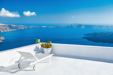Sunbed on the terrace of a hotel. Santorini island, Greece. Beautiful summer landscape with sea view