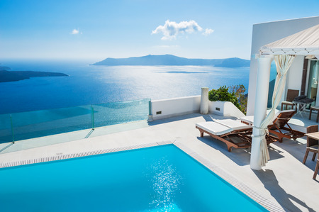 vacation destinations: White architecture on Santorini island, Greece. Swimming pool in luxury hotel. Beautiful landscape with sea view