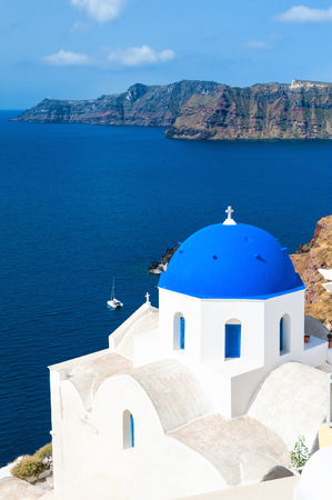 town idyll: Church with blue domes in Oia town, Santorini island, Greece. Beautiful landscape with sea view