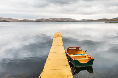 Żółty molo i żółta łódź na jeziorze. Jesienny krajobraz z widokiem na jezioro i góry Zdjęcie Seryjne