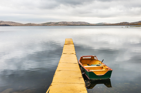 Yellow pier and yellow boat on the lake. Autumn landscape with lake and mountains views