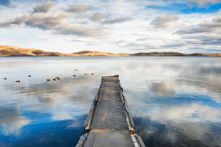lake: Old pier on the lake, a floating flock of ducks and the sky reflecting in the water. Autumn landscape with lake and mountains views Stock Photo
