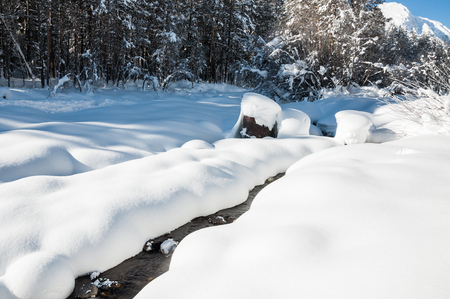 river: Snowfall on the mountain river. Beautiful winter landscape. Stock Photo