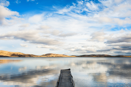 old pier: Old pier on the lake and the sky reflecting in the water. Autumn landscape with lake and mountains views