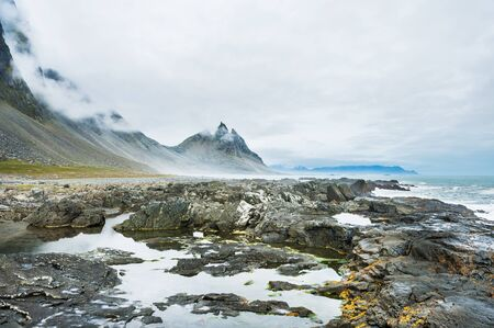 volcanic stones: Fantastic coast of the Atlantic ocean with volcanic stones and mountain view. Southern Iceland
