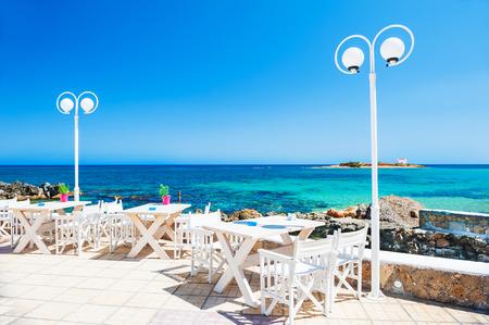 Beautiful tropical beach with turquoise water. Cafe on the beach. Malia, Crete island, Greece.