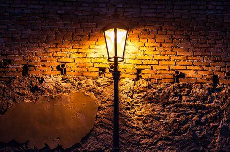 Uitstekende straatlantaarn tegen een rode bakstenen muur bij nacht