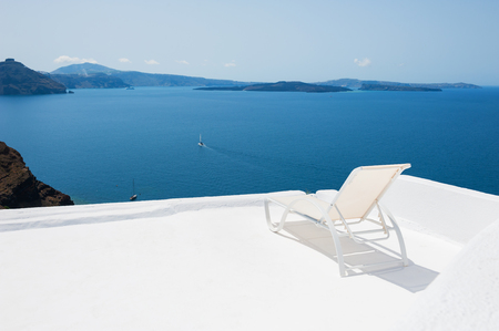 Deck chair on the terrace with sea view. White architecture on Santorini island, Greece. Stock Photo
