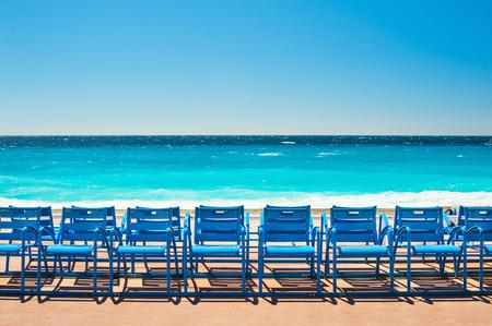 sillas azules en el Paseo de los Ingleses en Niza, Francia. Hermoso mar azul turquesa y la playa Foto de archivo
