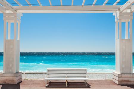 Bancos blancos en la Promenade des Anglais en Niza, Francia. Hermoso mar turquesa y playa