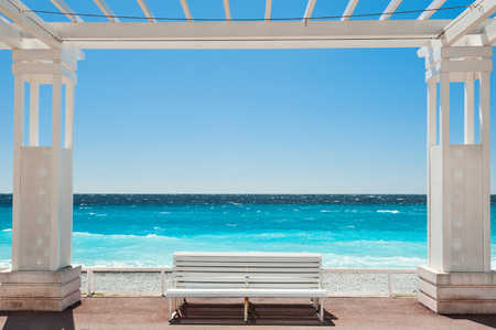 White benches on the Promenade des Anglais in Nice, France. Beautiful turquoise sea and beach Standard-Bild