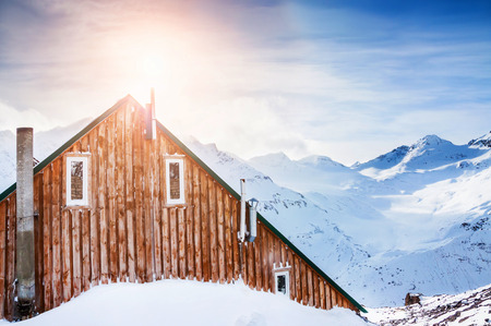 Wooden house in the mountains. Beautiful winter landscape with snow-covered mountains at sunset