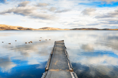 Old pier on the lake with floating ducks and sky reflecting in the water. Beautiful autumn landscape, tranquil scene