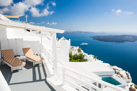 Beautiful terrace with chaise lounges, sea view. White architecture on Santorini island, Greece.