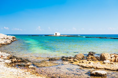 Beautiful beach and white chapel in the sea in Georgioupolis, Crete island, Greece Imagens