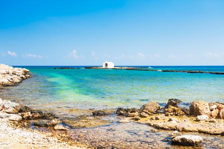 Mooi strand en witte kapel in het overzees in Georgioupolis, het eiland van Kreta, Griekenland