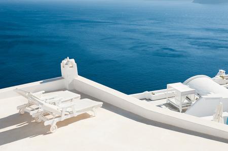 Two sunbeds on the terrace with sea views. Santorini island, Greece