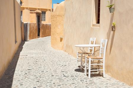 Table with two chairs on the cozy street in Santorini island, Greece. Zdjęcie Seryjne