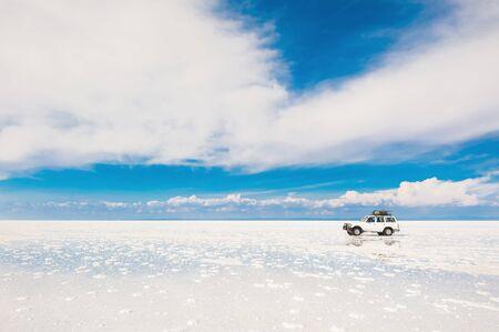 Salar de Uyuni, Bolivia - March, 26, 2017: Off-road car driving through the salt flat Salar de Uyuni in Bolivia