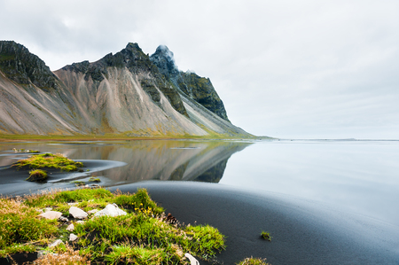 Mountains and reflections on the shore of Atlantic ocean in eastern Iceland