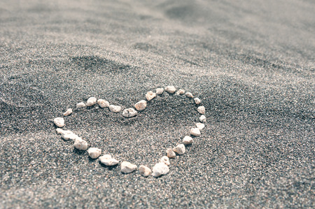 Stones in the shape of heart on the black sandy beach. Shallow depth of field 写真素材