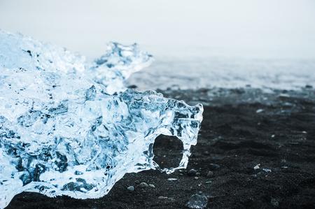 Blue ice on the black volcanic beach. Jokulsarlon ice beach, Iceland. Фото со стока