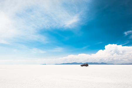 Off-road car driving on Salar de Uyuni salt flat in Bolivia