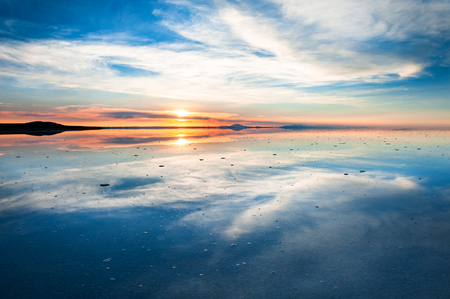 Mirror surface of Salar de Uyuni salt flat at sunrise. Altiplano, Bolivia